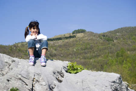 little girl sitting: A girl sitting on a rock Stock Photo
