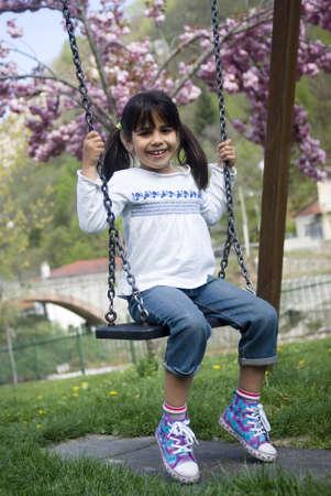 Happy girl on swing photo