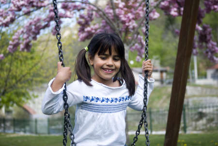 Young girl sitting on swing photo