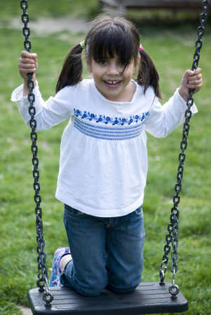 Young girl standing on swing, smiling photo