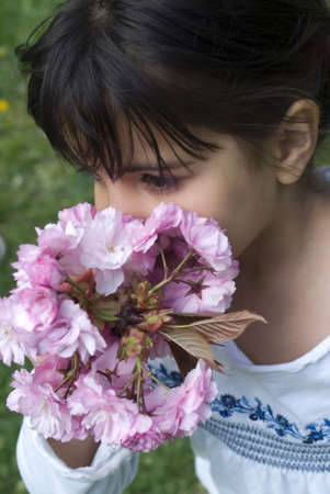 Girl smelling pink flowers of fruit tree photo