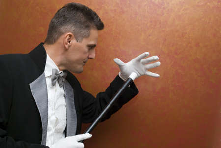 deceiving: Magician performing with wand Stock Photo
