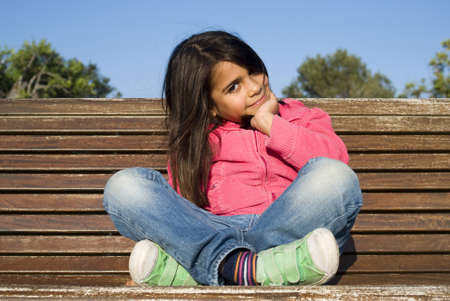 6 years girl: The little girl sitting on bench
