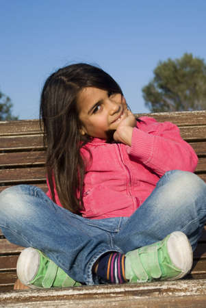 The little girl sitting on bench photo