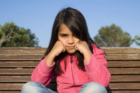 The little girl sitting on bench Stock Photo - 11487241