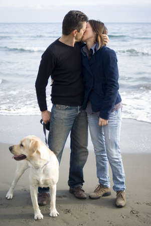 Romantic couple on beach with dog photo