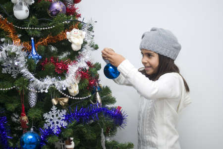 decorating christmas tree: Lovely preschool girl decorating Christmas tree
