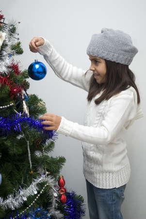 Girl putting ornament on Christmas tree photo