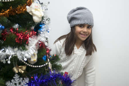 Girl behind Christmas tree photo