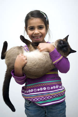 baby girls smiley face: Little girl with siamese cat