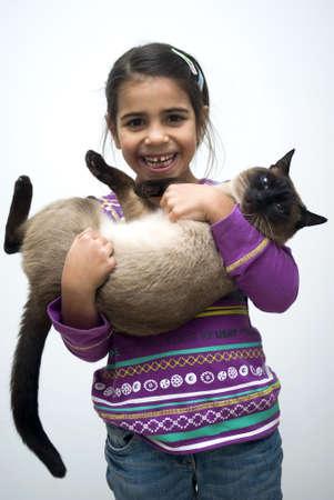 Niña con gato siamés Foto de archivo