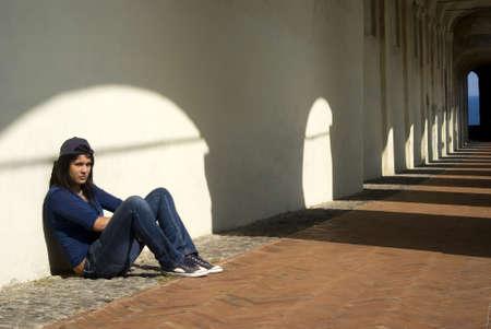 verdrietig meisje: Droevig meisje zitten tegen een muur