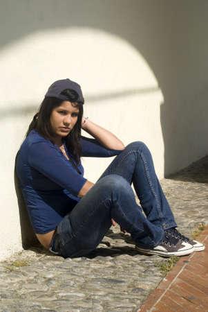 Sad girl sitting against a wall
