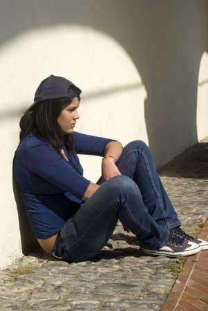 teenage problems: Muchacha triste sentado contra una pared