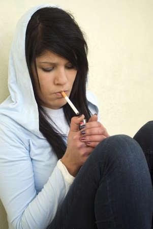 La muchacha está encendiendo un cigarrillo