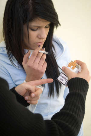 joven fumando: Chico tratando de dejar de fumar ni�a Foto de archivo