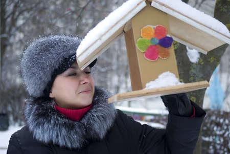 Woman examining a birdhouse in city park Stock Photo - 12203177