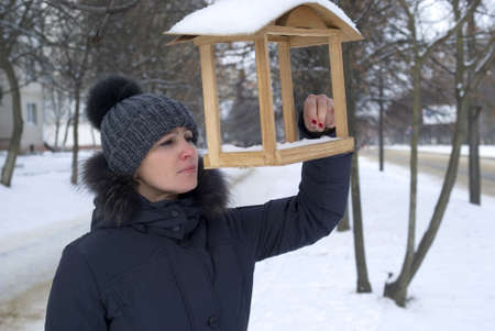 Woman examining a birdhouse in city park photo