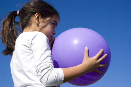 girl blowing: Girl blowing up balloon Stock Photo