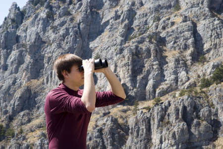 explores: Mountain hiker looking through binoculars Stock Photo