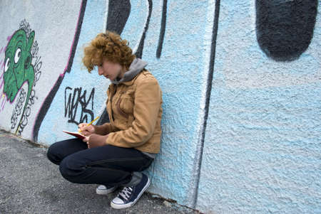 Girl sitting against a graffiti wall and written photo