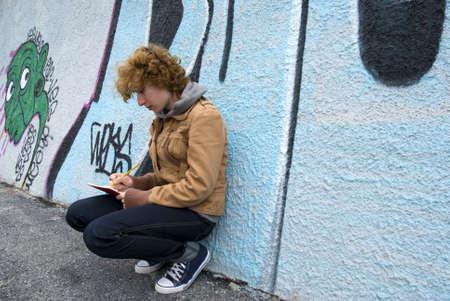 Girl sitting against a graffiti wall and written photo