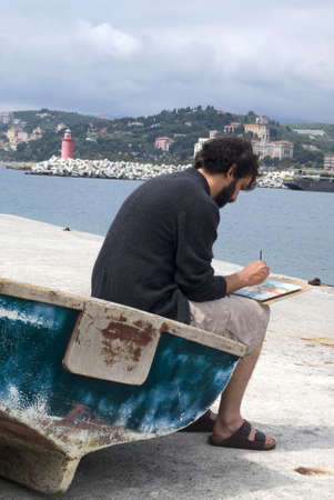Painter painting a picture sitting on old row boat on the pier photo