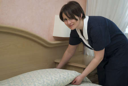 Maid making hotel bed photo