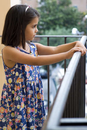 Girl standing on the balcony of home photo