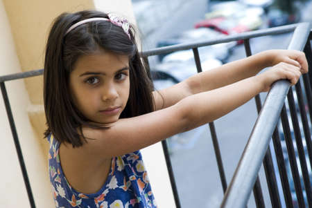 Girl standing by a railing of the balcony photo