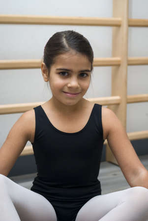 Happy ballerina sitting on floor in dance class photo