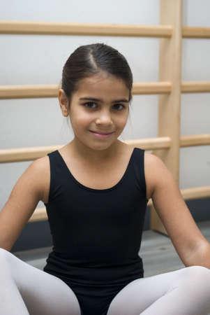 only teenage girls: Happy ballerina sitting on floor in dance class Stock Photo