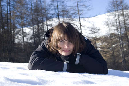 Smiling woman laying in snow photo
