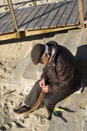 Nazare, Atlantic coast of Portugal - November 24, 2010: Senior fisherman is repairing  fishing net on the beach