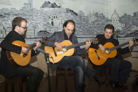 melodious: Lisbon, Portugal - November 23, 2010: Fado - playing a traditional portuguese guitar. Performing in a Lisbon cafe �Luso� - typical restaurant with fado and folklore Editorial