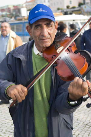 Coimbra, Portugal – November 25, 2010: Elderly man busker playing violin on the street