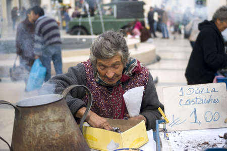 Coimbra, Portugal � November 25, 2010: Poor elderly woman sells chestnuts on the street of city