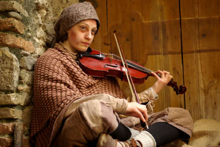 Taggia, Italy – February 28, 2010: Participant of medieval costume party. This image:  Young violinist