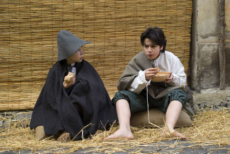 Taggia, Italy � February 27, 2011: Historical reenactment participants. This image: Poor children in the street
