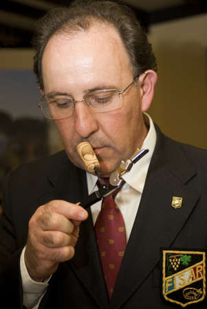 sommeliers: Verona, Italy – April 8, 2011: Sommelier of FISAR (Federation of Italian Sommeliers Hotel Keepers and restaurateurs) sniffing the cork from wine during International wine exhibition at Vinitaly (April 7-11, 2011 in Verona, Italy)