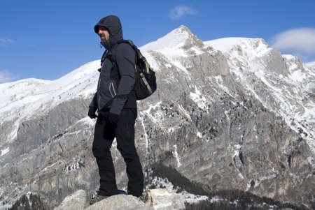 Mountain climber standing on peak photo