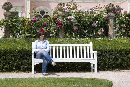 A woman sitting at a garden bench photo