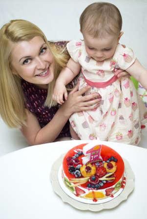 Happy mother with her baby celebrating birthday photo