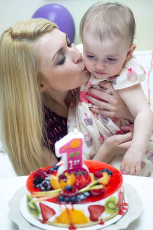 Mother and baby with birthday cake  photo