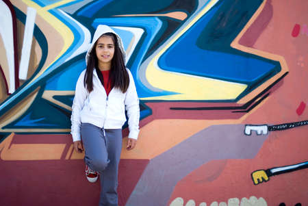 Girl standing against graffiti wall photo