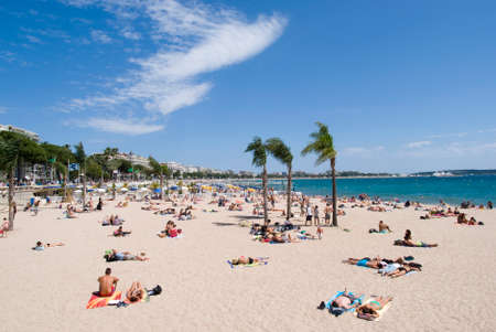 Cannes, France � June 5, 2014  People relaxing on the beach in Cannes - the city of famous tourist destination in the French Riviera