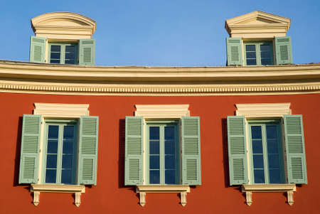 nice  france: Nice, France, September 29, 2014: Colourful house wall with windows in Mediterranean style