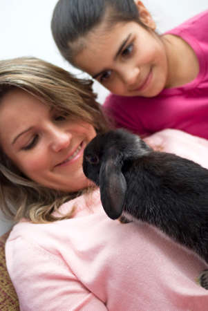 35 40 years: Mother and daughter playing with pet rabbit at home