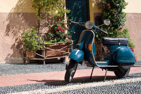 vespa piaggio: Scooter Classico parcheggiato in via Archivio Fotografico