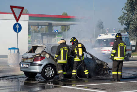 piacenza: Piacenza, Italy  November 1, 2015: Italian firefighters extinguishing car on fire parked in a gas station, Piacenza, Northern Italy Editorial